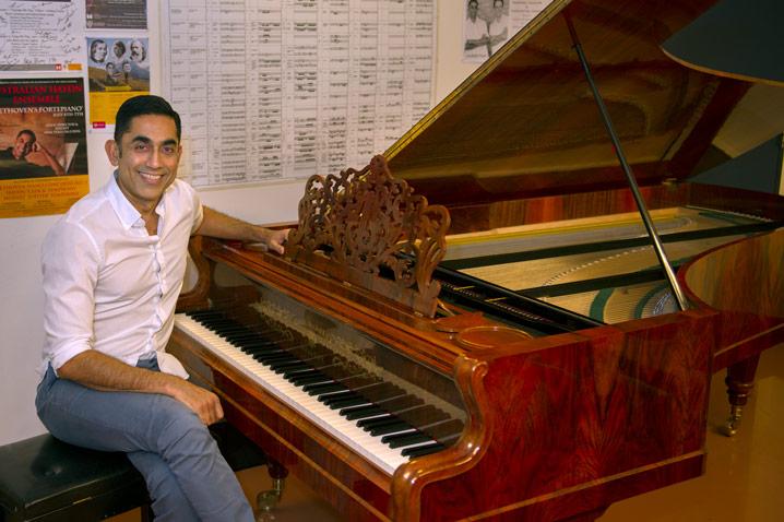 Professor Neal Peres Da Costa sitting on his piano.