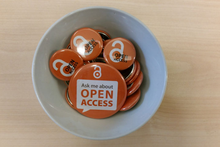"Open Access badges in a bow on the table. The one in the middle says: ""Ask me about open access"""