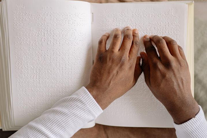 photo of hands reading braille